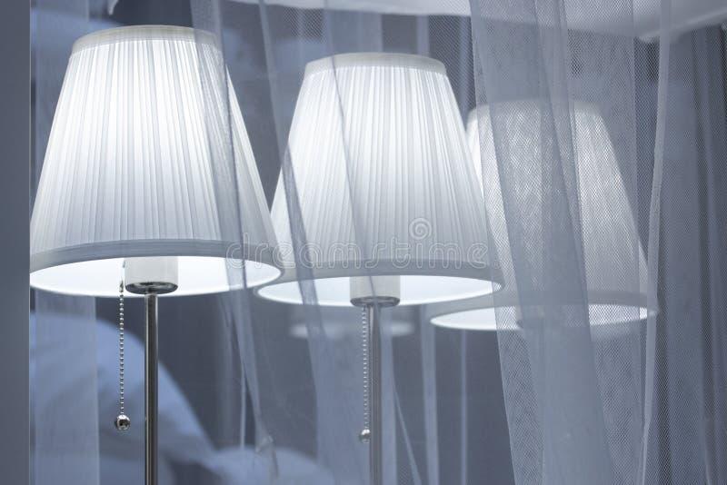 Tischlampe mit einem leichten Glühen sind der dünne Schleier von Tulle-Vorhang, Hintergrund, gemütliche Beleuchtung des Fotos stockfotografie