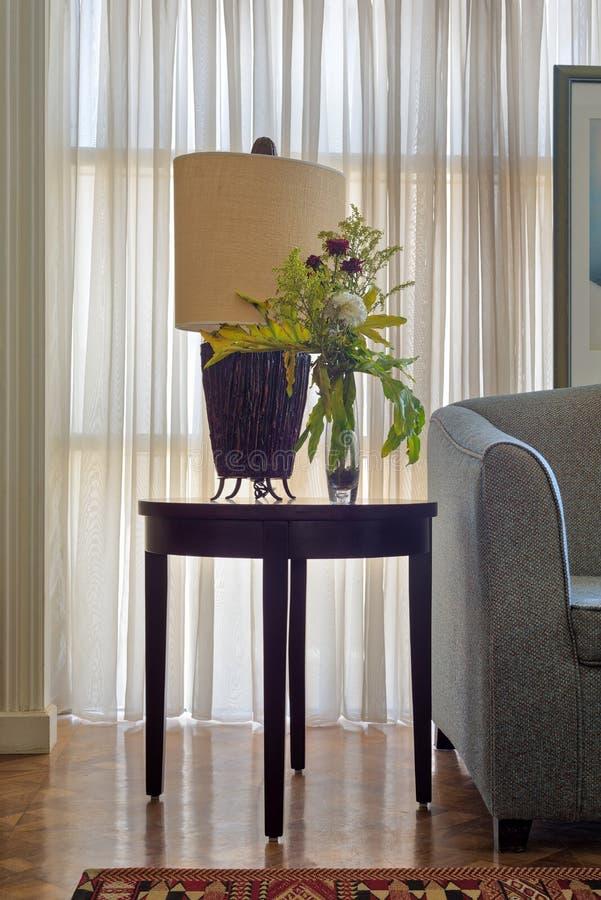 Tischlampe und bunter Blumenpflanzer auf kleinem dunkelbraunem Holztisch auf Hintergrund des großen Fensters mit weißen bloßen Vo stockfotografie