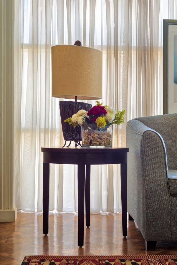 Tischlampe und bunter Blumenpflanzer auf kleinem dunkelbraunem Holztisch auf Hintergrund des großen Fensters mit weißen bloßen Vo lizenzfreies stockbild