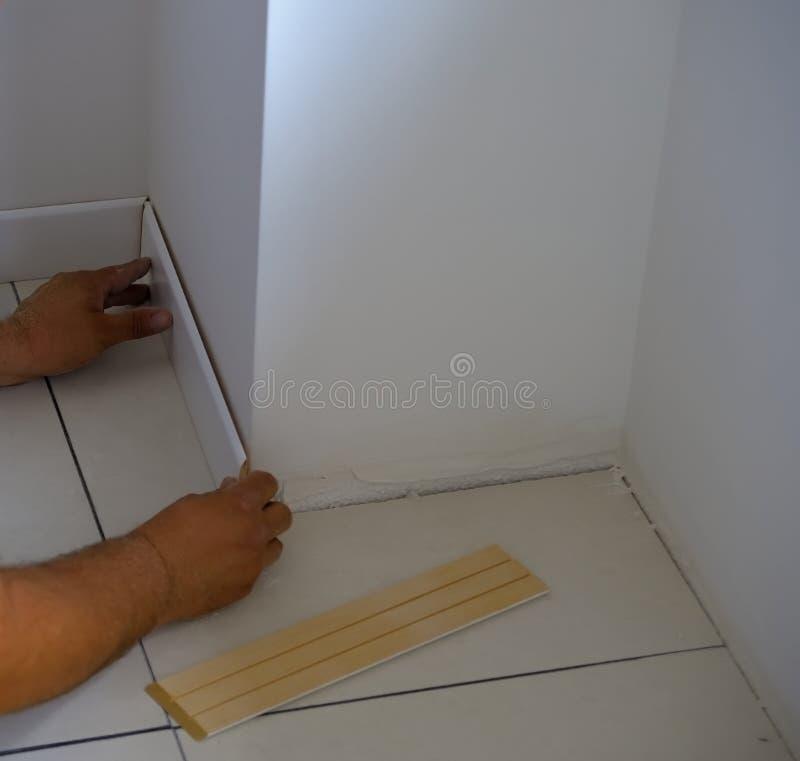 Tischler auf der Arbeit, die hölzerne Fussleiste mit Kleber setzt lizenzfreies stockbild