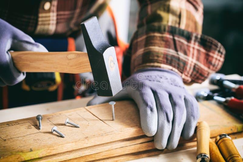Tischler, der einen Hammer hält lizenzfreie stockbilder
