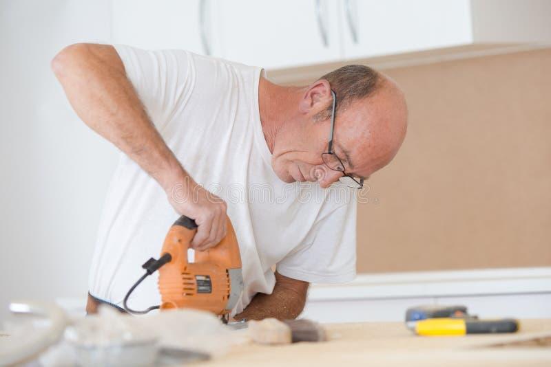 Tischler, der elektrische Säge verwendet, um Holz zu schneiden stockfoto