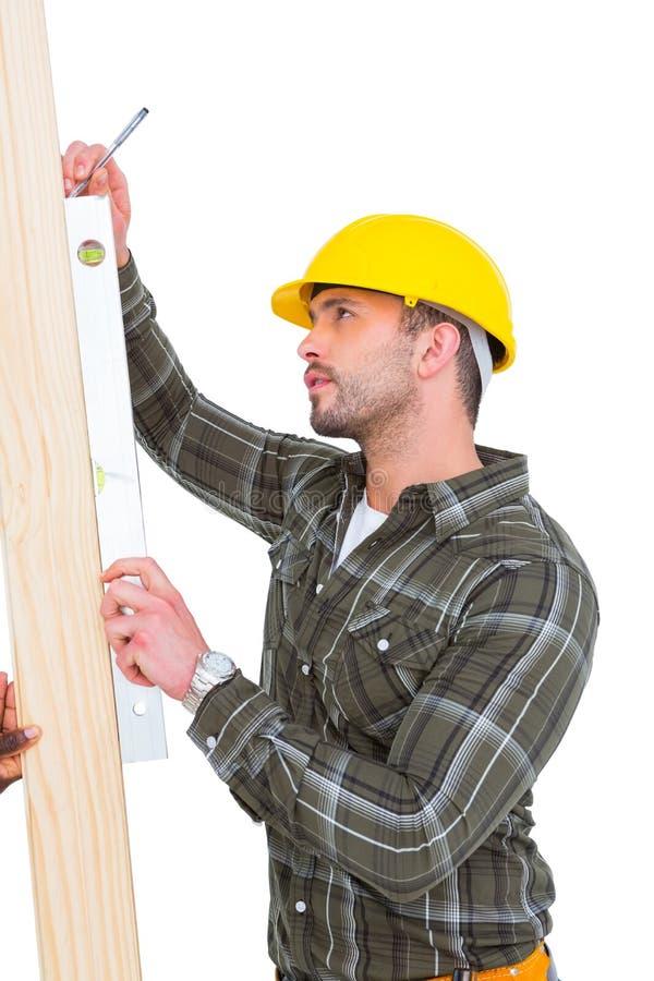 Tischler, der Geistniveau auf hölzerner Planke verwendet stockbilder