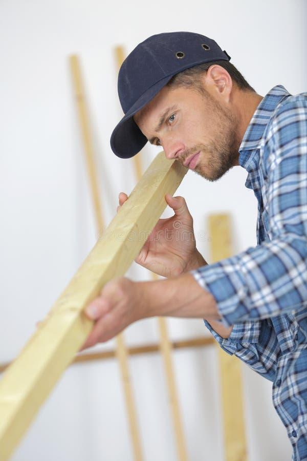 Tischler, der gerade Holz überprüft lizenzfreies stockbild