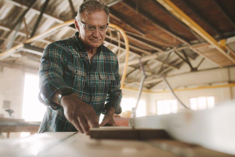 Tischler, der hölzerne Planken in der elektrischen Säge schneidet stockfoto