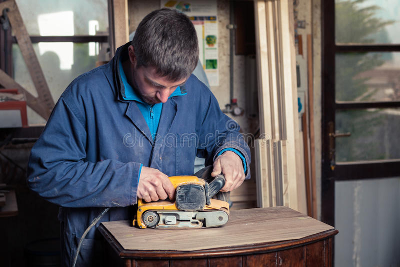 Tischler, der Möbel mit Bandschleifmaschine wieder herstellt lizenzfreie stockbilder