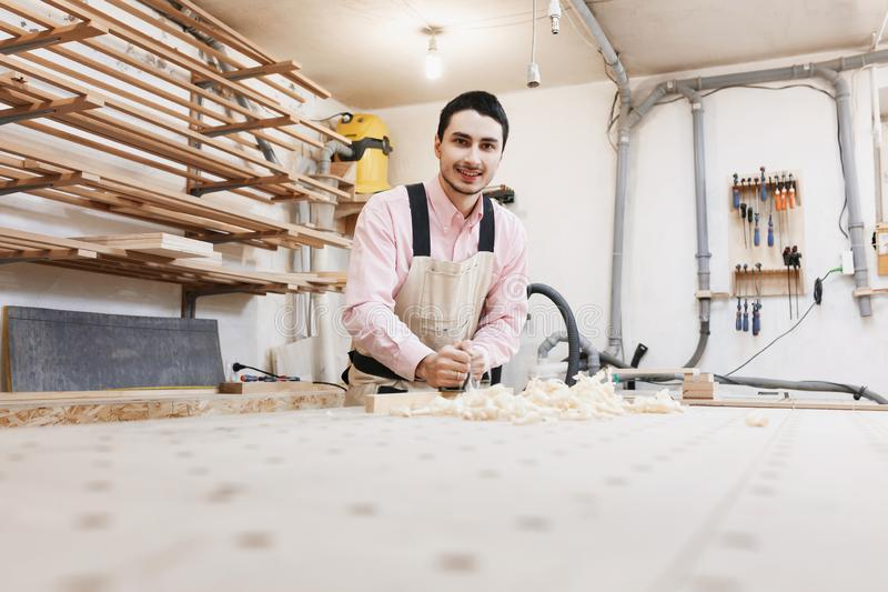 Tischler, der mit Fläche und hölzerner Planke an der Werkstatt arbeitet stockfoto