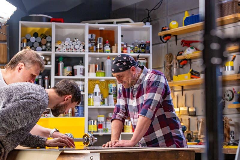 Tischler, der seine Arbeit in der Zimmereiwerkstatt erledigt ein Mann in einer Zimmereiwerkstatt misst und im Schnittlaminat stockbild