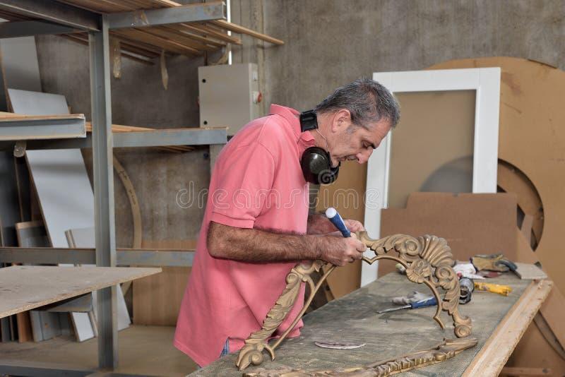 Tischler, der in seiner Werkstatt arbeitet stockbilder