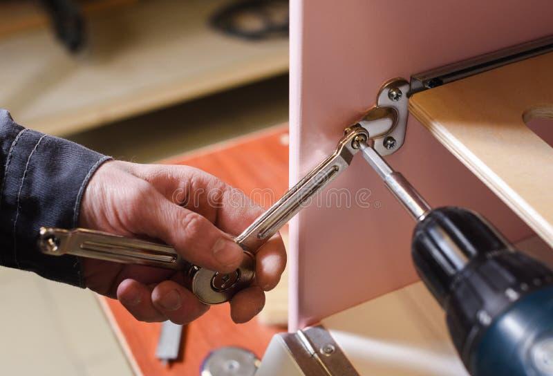 Tischler, der an Spielmöbeln arbeitet Reparierenclosers auf Spielküchen-Ofentür mit Schraubenzieher stockbild