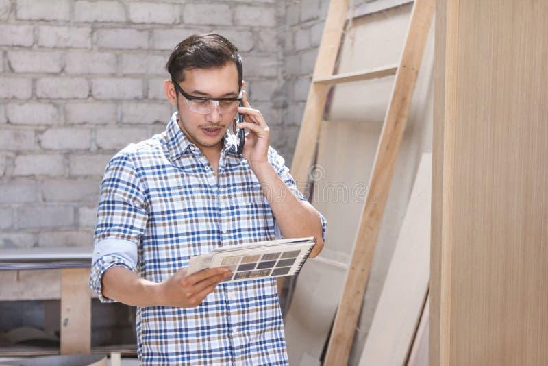 Tischler, der am Telefon mit seinem Kunden beim an schauen spricht lizenzfreies stockfoto