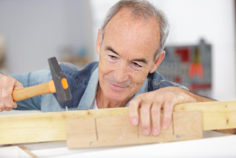 Tischler des älteren Mannes, der mit Hammer arbeitet lizenzfreie stockfotografie