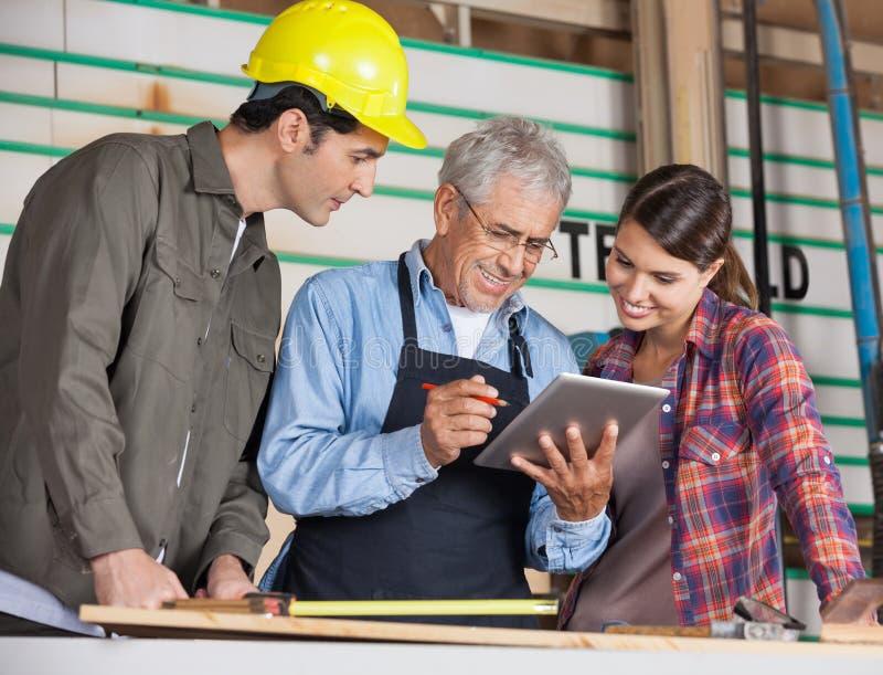 Tischler, die Tablet-Computer in der Werkstatt verwenden stockfoto