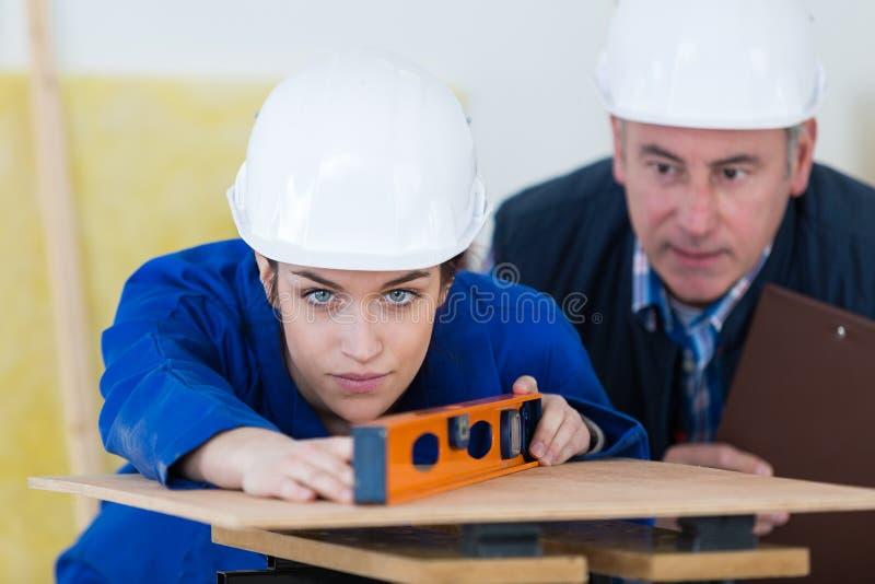 Tischler With Female Apprentice, das an Baustelle arbeitet lizenzfreie stockfotografie