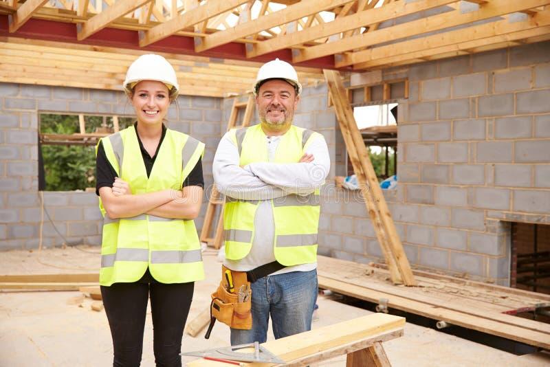 Tischler With Female Apprentice, das an Baustelle arbeitet lizenzfreie stockbilder