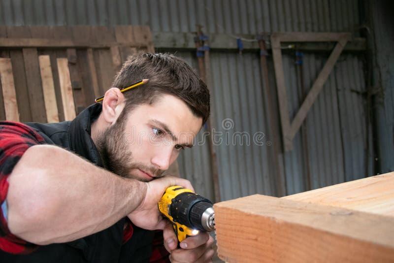 Tischler, hölzerne Arbeitskraftarbeit, die Bauholzprodukt misst, bohrt und macht stockfotos