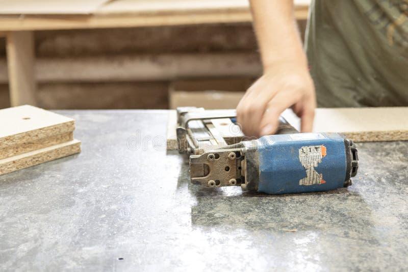 Tischler hebt einen Bolzenschussapparat für Heftklammern an lizenzfreie stockfotos