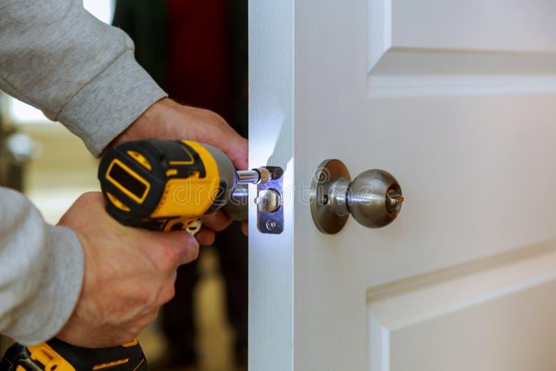 Tischler Install Door Lock, das zu Hause Schraubenzieher verwendet lizenzfreie stockbilder