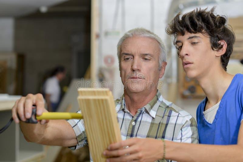 Tischler mit messendem Holz des Lehrlings lizenzfreie stockbilder