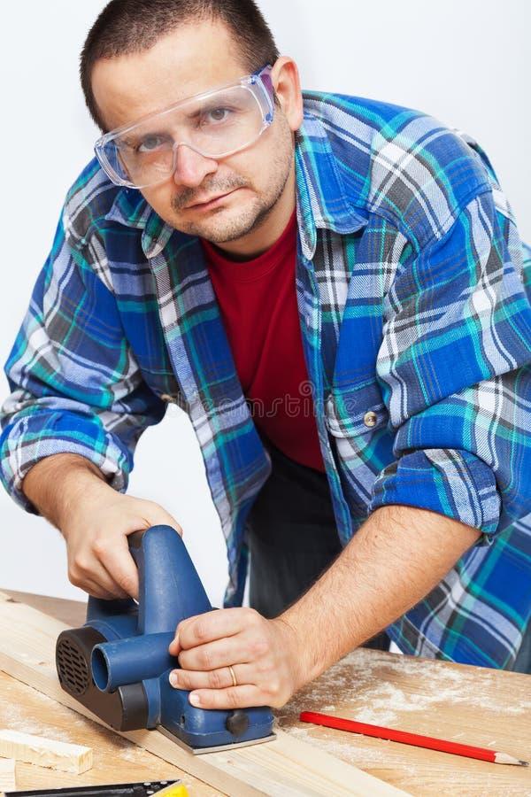 Tischler oder Schreiner, die mit elektrischem Hobel arbeiten stockfotografie
