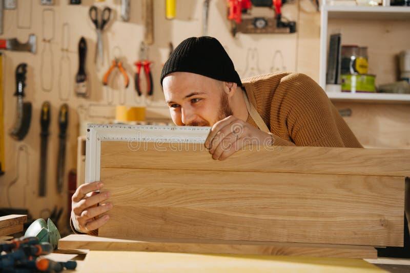Tischler stellt Möbel auf Auftrag in einer Werkstatt her lizenzfreie stockbilder