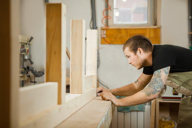 Tischler tut Maße entsprechend Projekt Tischlerswerkstatt stockbild
