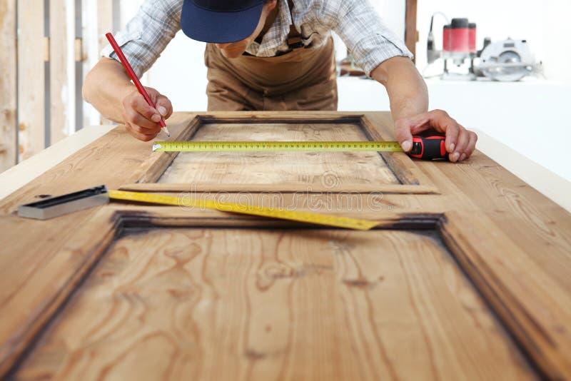 Tischlerarbeit das Holz, eine hölzerne Weinlesetür messend stockbilder