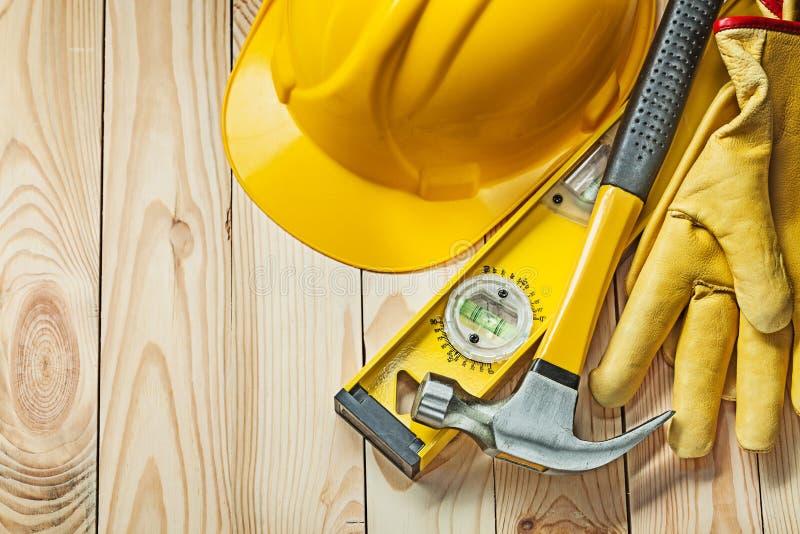 Tischlerhammerbau-Niveaulederhandschuhe und Bausturzhelm auf Holz lizenzfreie stockfotos
