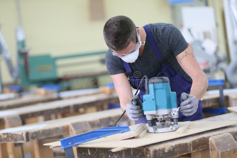 Tischlerlehrling, der an Holz arbeitet stockfotografie