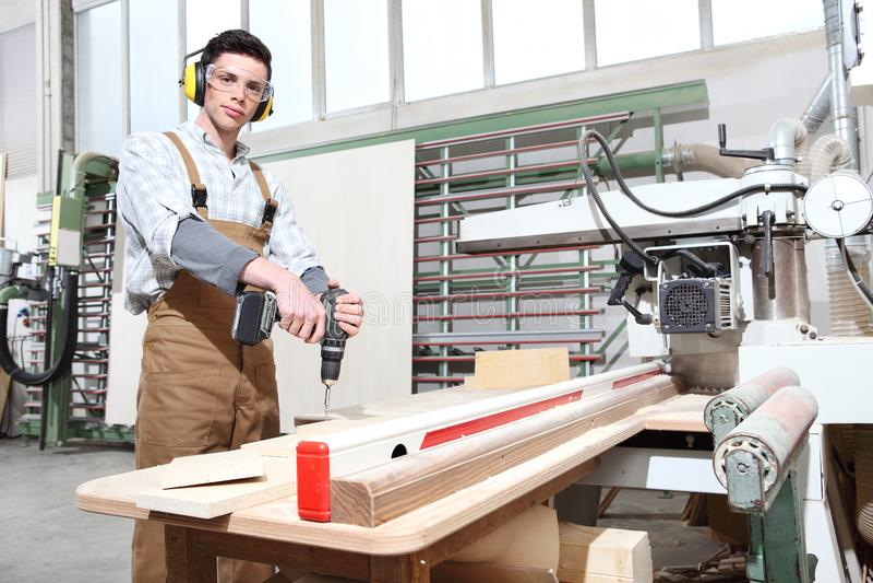 Tischlermannarbeit in der Zimmerei, mit drahtloser Bohrgerätfahrerschraube ein Brett, geschützt mit Ohrmuffen stockfotos