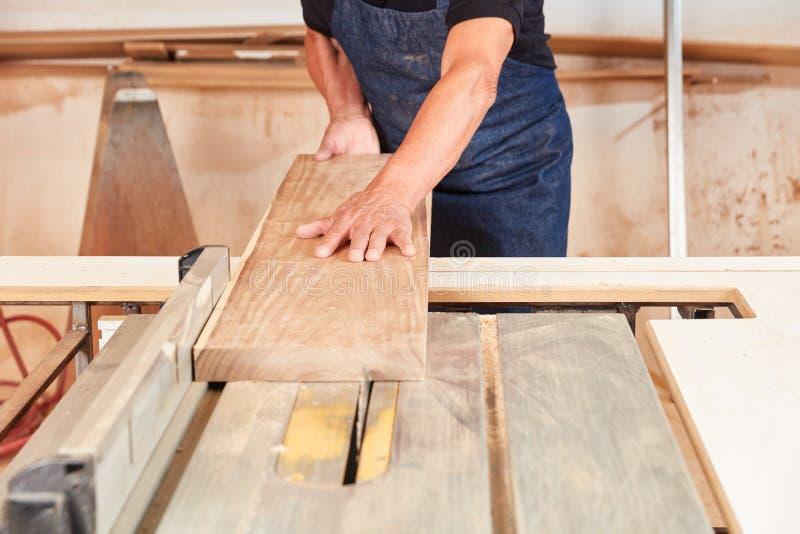 Tischlersägen ein hölzernes Brett an der Kreissäge lizenzfreie stockfotos