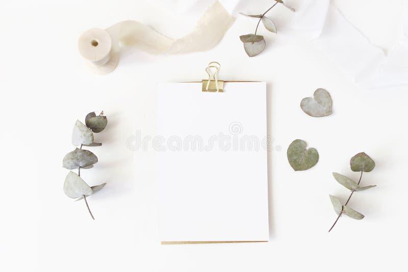 Tischplattenbriefpapiermodell der weiblichen Hochzeit mit leerer Grußkarte, trockenen Eukalyptusblättern, Seidenband und Goldenem stockfotografie