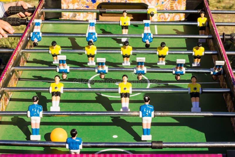 Tischplattenfußballspiel mit einem grünen Feld und blauen und gelben Rivalen stockfotografie