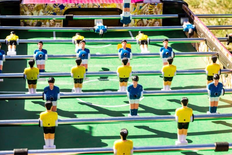 Tischplattenfußballspiel mit einem grünen Feld und blauen und gelben Rivalen lizenzfreies stockbild