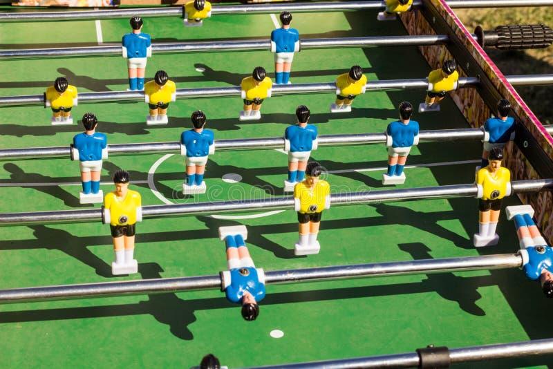 Tischplattenfußballspiel mit einem grünen Feld und blauen und gelben Rivalen stockfotos
