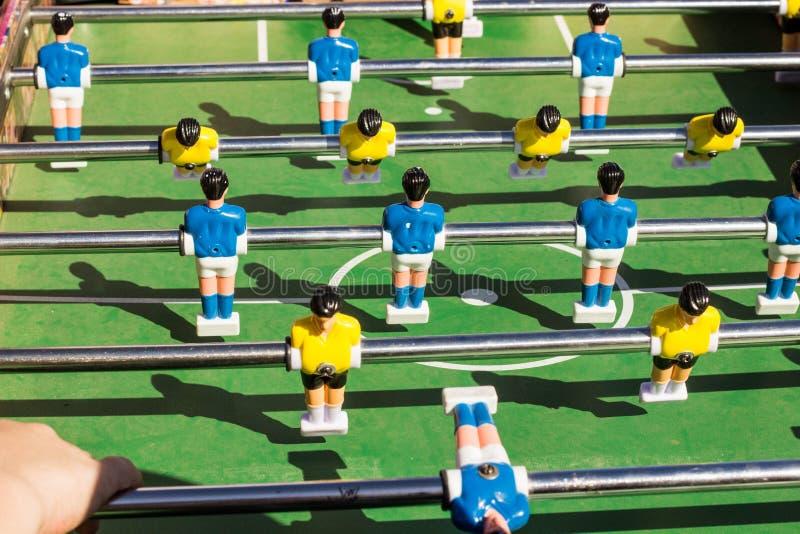 Tischplattenfußballspiel mit einem grünen Feld und blauen und gelben Rivalen stockfoto