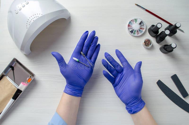 Tischplattenmaniküre Verschiedene Elemente für Nagelentwurf Der Meister hält in seinen Händen die Schneider für das Entfernen des stockbild