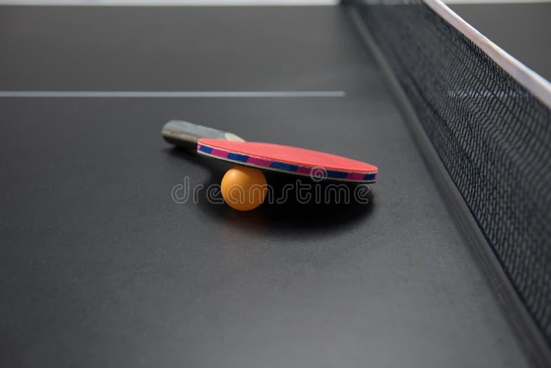 Tischtennisschläger mit orange Kugel stockbild
