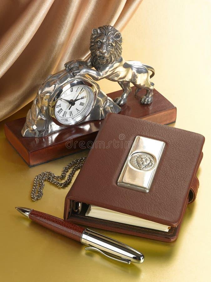 Tischuhr mit einer Zahl eines Löwes und des Tagebuchs mit dem Bild eines Löwes lizenzfreie stockbilder