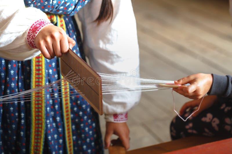 Tissage et fabrication de la fin faite main de tissu  les mains du ` s de femmes derrière un métier à tisser font le tissu photos libres de droits