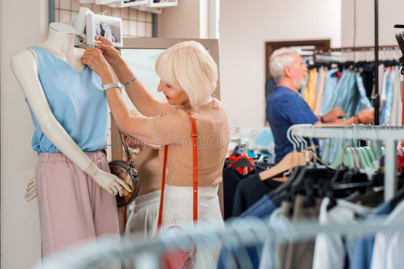 Tissu émouvant de vêtements de femme agée positive au magasin d'habillement photo libre de droits