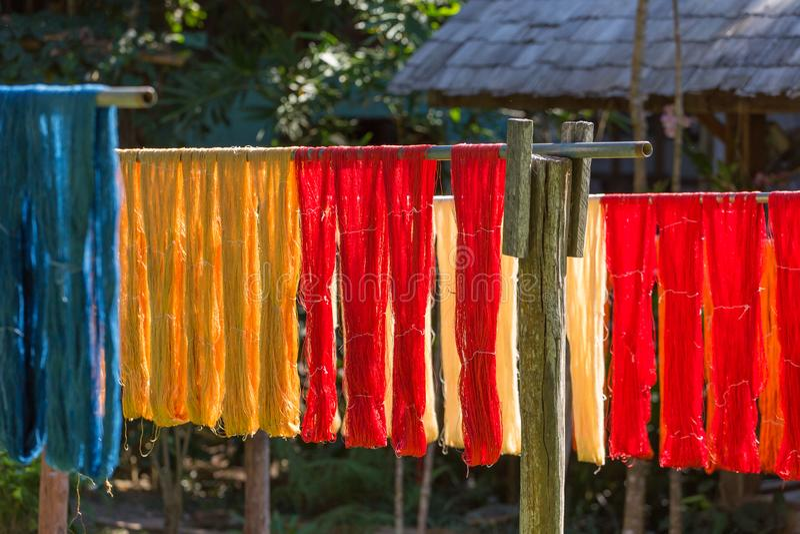 Tissu coloré accrochant pour sécher après processshot traditionnel de colorant dans Luang Prabang images stock