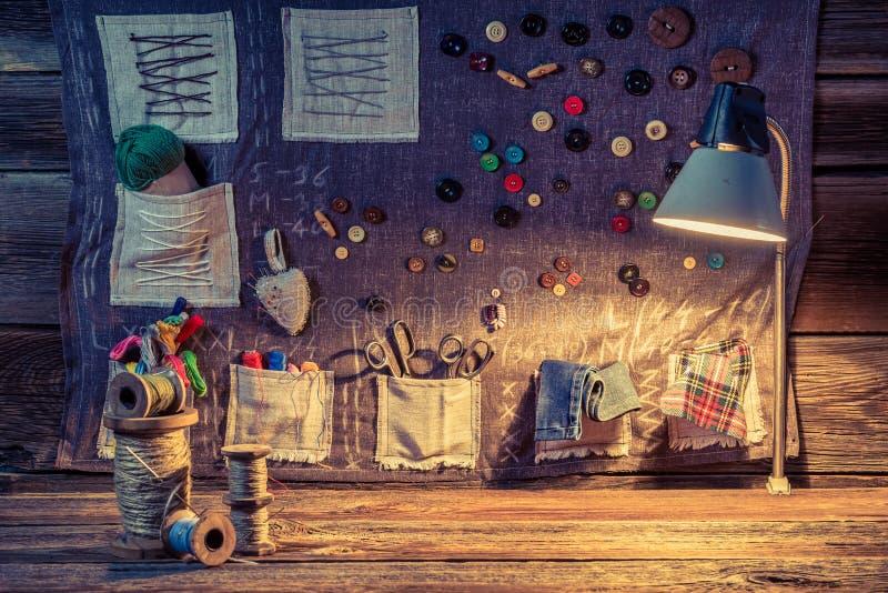 Tissu de couture fait de fils, aiguilles et boutons dans l'atelier de tailleur illustration libre de droits