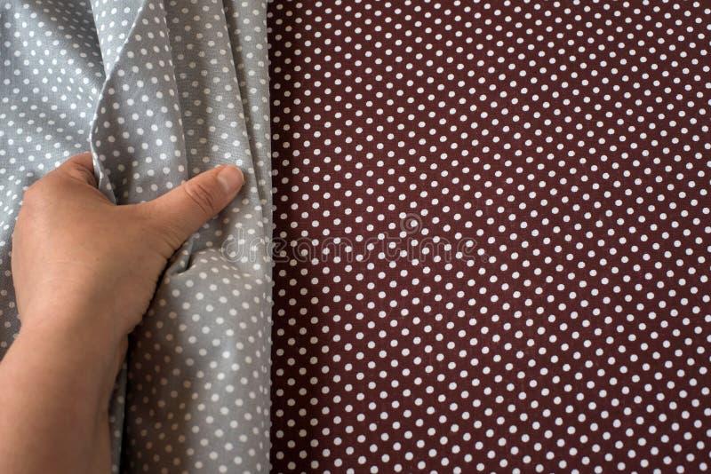 Tissu gris émouvant de main femelle sur le tissu brun comme fond Avec l'espace de copie photo libre de droits