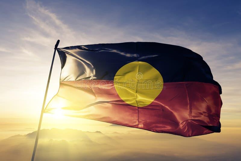 Tissu indigène australien de tissu de textile de drapeau ondulant sur le brouillard supérieur de brume de lever de soleil illustration stock