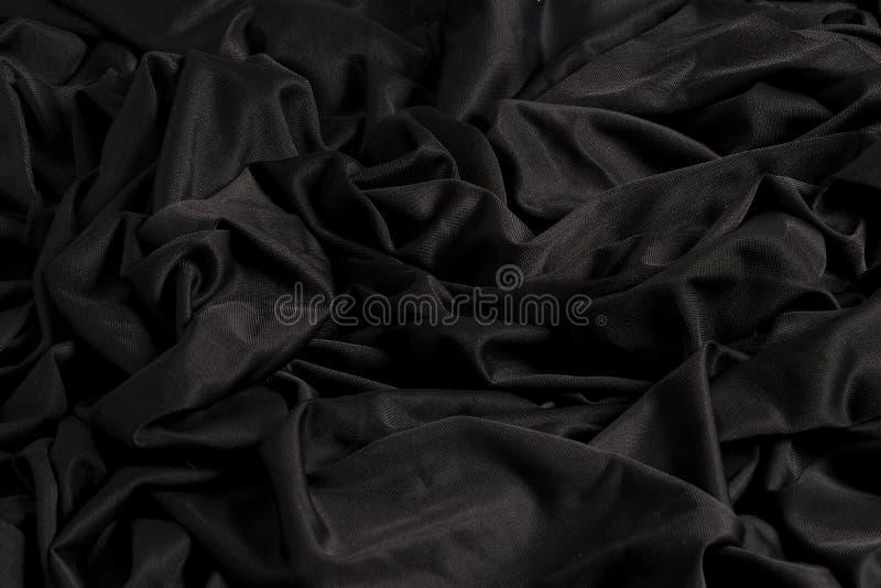 Tissu noir lumineux avec des ondulations et la texture avec la lumière dure et la lumière foncée photos libres de droits