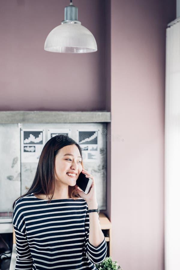 Tissu occasionnel d'usage de propriétaire de femme d'affaires de l'Asie parlant sur le pho mobile photographie stock