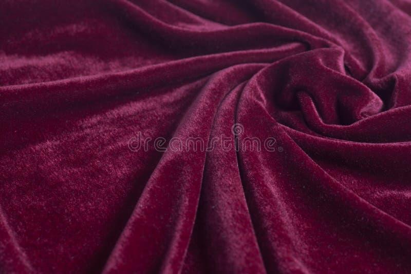 Tissu rouge de velours avec les plis en spirale images stock
