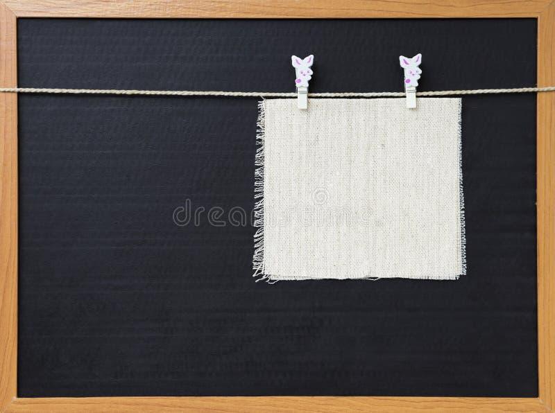Tissu vide de toile accrochant sur la ficelle au-dessus du fond noir photos libres de droits