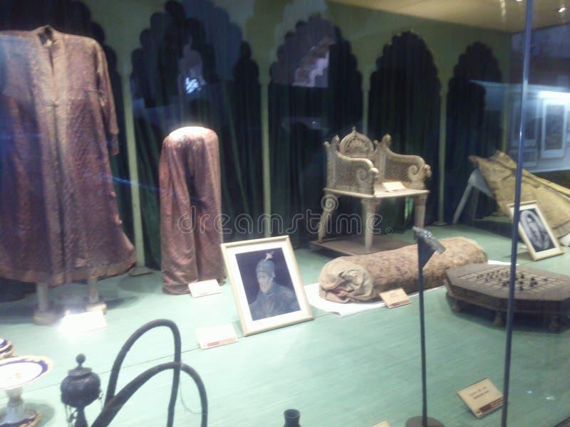 Tissus, chaises, chasses, oreiller, table et ciger historiques photographie stock libre de droits